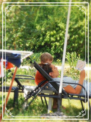 Une maman et son enfant dans le jardin. elle lui fait raconte une histoire