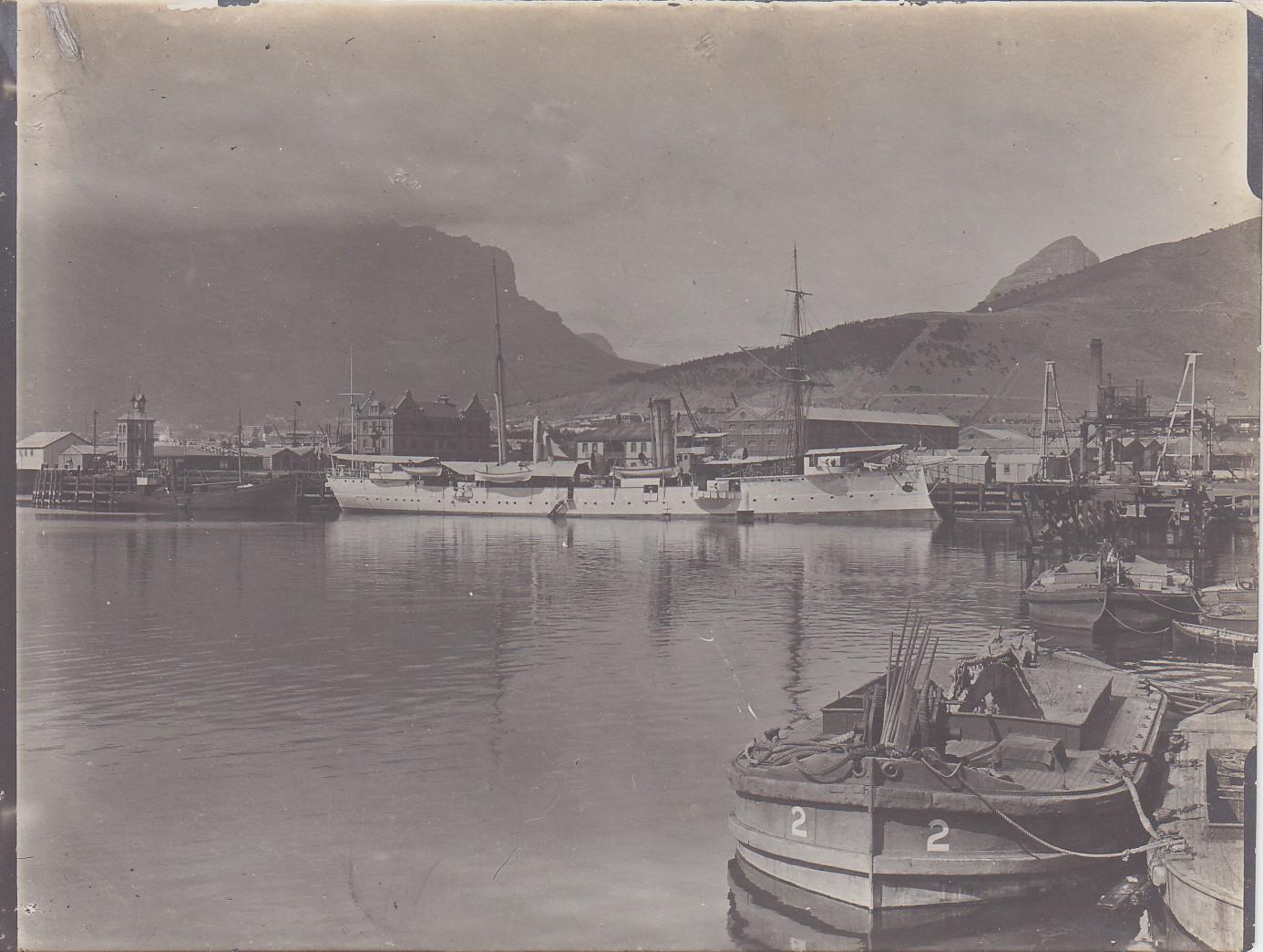 """SMS Seeadler in Kapstadt an der Pier (2. Feb. - 8. März) - links der Tafelberg und rechts """"Signal-Hill"""""""