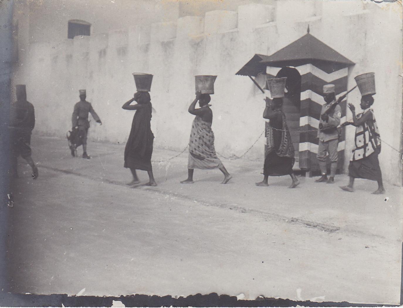 Weibliche Sträflinge an der Kette - vor dem Gebäude der Polizei-Askaris (Gefängnis und zugleich Kaserne der Polizei-Askaris in Daressalam)
