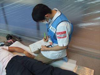 カルテを記入する小河原鍼灸師、構造改善センターにて