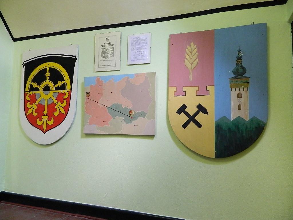 Die Wappen, Voerde (l), Krickerhau (r). Dazwischen: Patenschaftsurkunde (l), Charta der Heimatvertriebenen