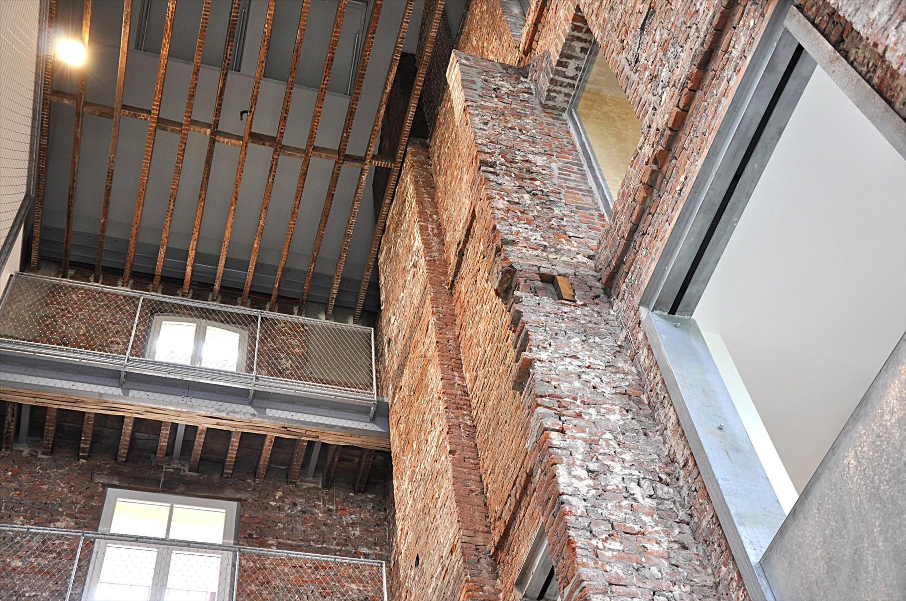 Caractéristiques de l'habitation familistérienne : construction en briques,coursives suspendues accessibles par des escaliers d'angles