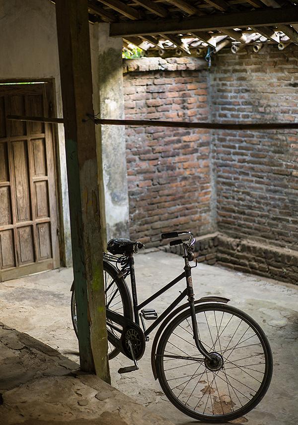 Reisefotografie: In der halboffenen Scheune wird normalerweise Reis gelagert. Jetzt steht hier nur ein altes Fahrrad. LEICA M9, mit ZEISS Biogon 2,0/35 mm, Foto: Klaus Schoerner