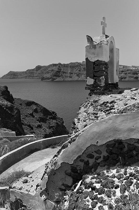 Seitenansicht der alten Kapelle von Ammoudi mit Blick auf Thirassia im Hintergrund.