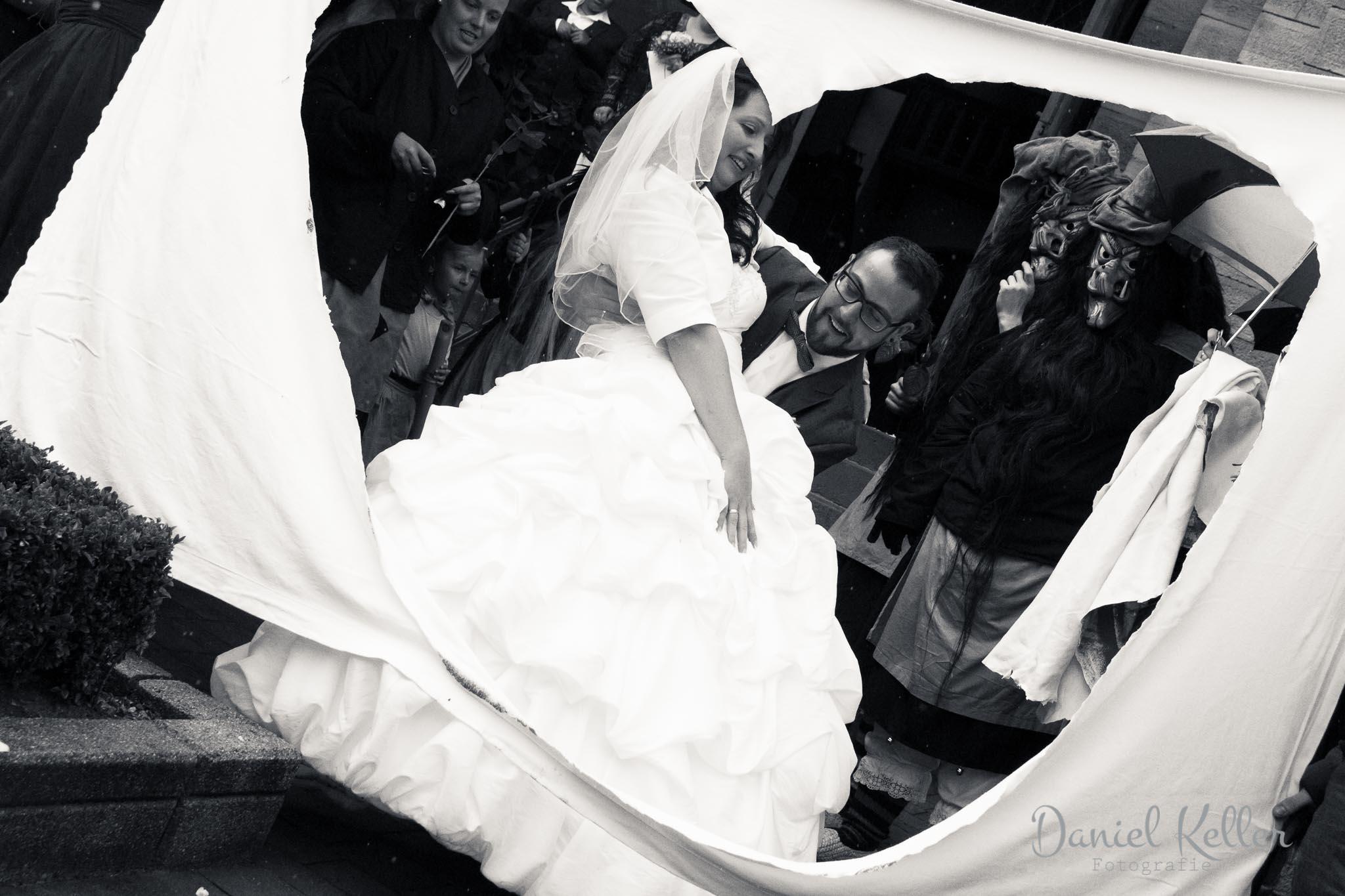 Bräutigam trägt Braut auf Händen durch ausgeschnittenes Herz