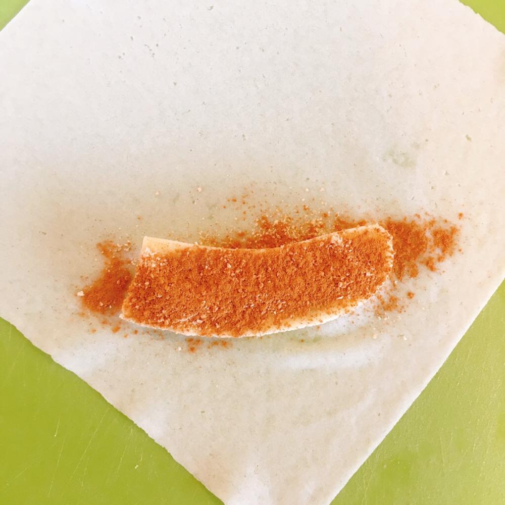春巻きの皮の上において砂糖とシナモンパウダーをかけます。