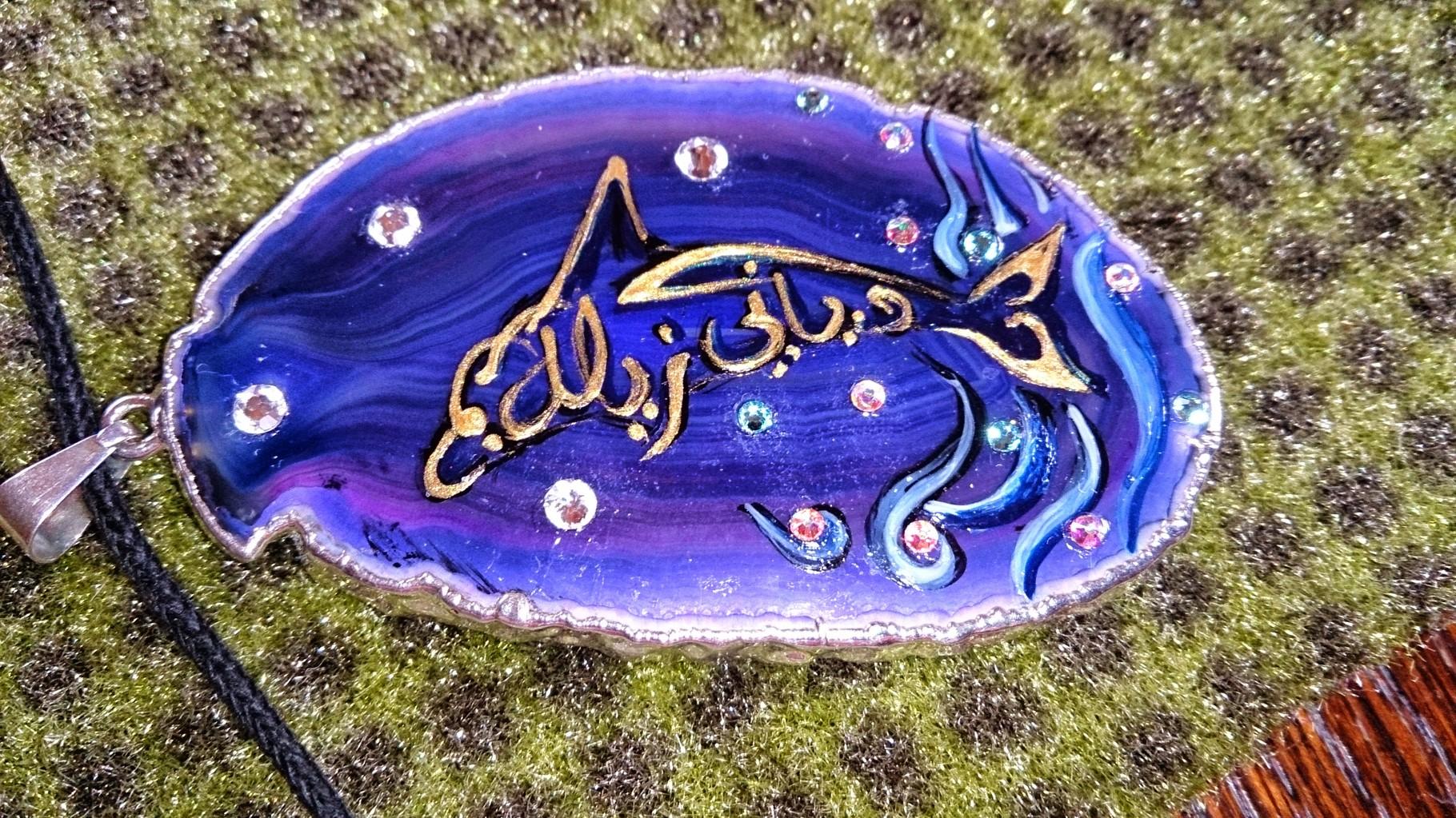 ~ Bild: Delfin-Anhänger mit arabischer Kalligrafie, Namenszug 'Silke Nur Adiani', grüner Teppich-Hintergrund ~