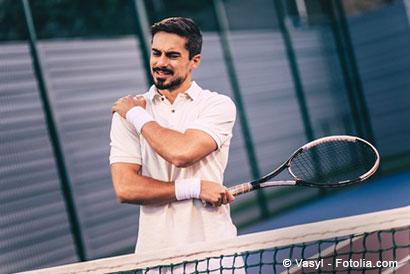 Junger Mann beim Tennis hält sich die Schulter