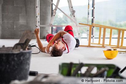 Bauarbeiter hält sich am Boden liegend die Schulter nach einem Sturz von der Leiter