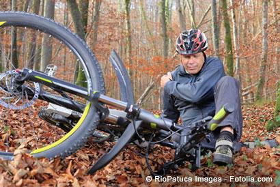 Älterer Mann hält sich die Schulter nach einem Sturz mit dem Mountainbike