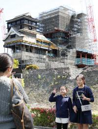 修復作業中の熊本城を背に記念写真に納まる観光客