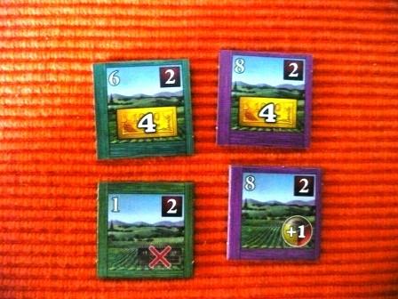 Das sind Weinberg Plättchen. Die oberen beiden zeigen den Preis an, den solch ein Plättchen kostet. Die beiden unteren zeigen die Regionen Seite an. Also die Seite, mit der das Plättchen auf meinem Spieltableau liegt.