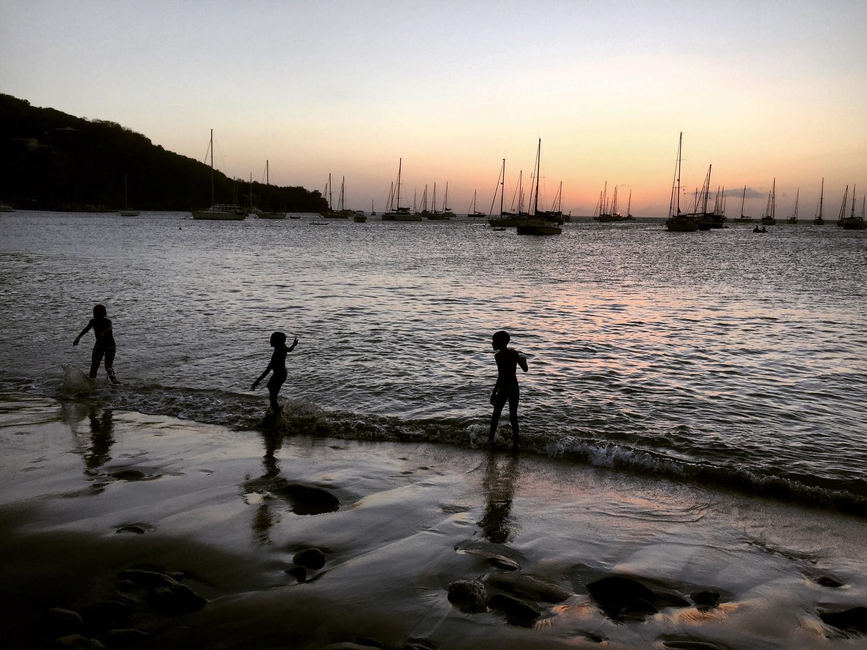 Enfants se baignant au coucher du soleil