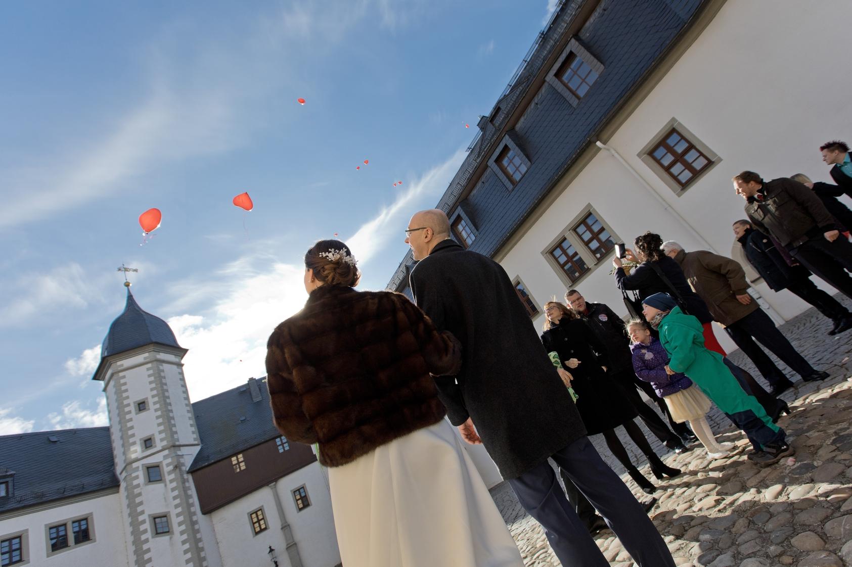 Brautpaar im Schlosshof von Schloss Wildeck in Zschopau lässt Luftballons in den Himmel steigen.