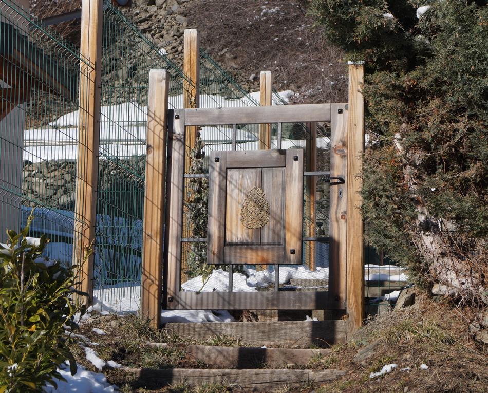 Portail de jardin ou de maison, à Orelle,  ayant une pomme de pin sculptée dans du bois