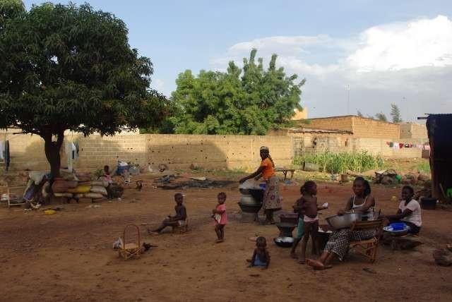 Dans la cour, les femmes travaillent et les enfants jouent