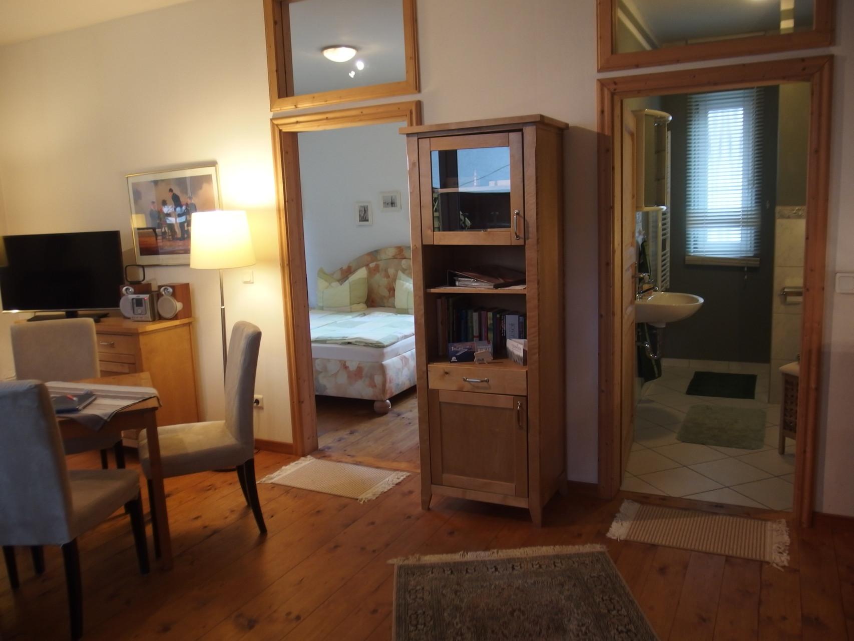 Wohnbereich mit Blick ins Schlafzimmer und Bad