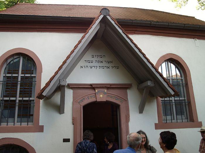 """Eingang in den Betsaal mit Portalinschrift: """"Der Ort, auf dem du stehst,  ist heiliger Boden"""" (2. Mose 3,5)"""