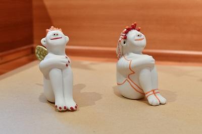 """2 sitzende Figuren """"Happy"""", von Margit Russnig, a 52.-"""