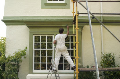 painter standing on scaffolding for exterior painting