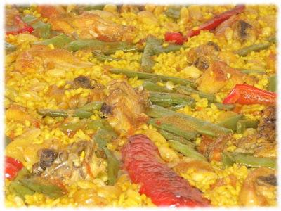 Cocina valenciana de paella de arroz con pimientos, conejo y pollo.
