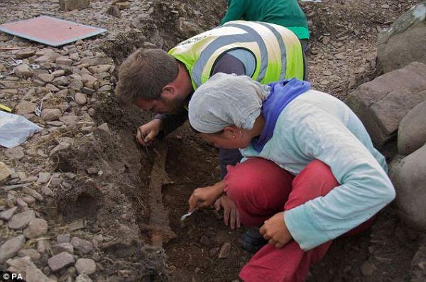 Oliver Harris examine une épée sur le site. Crédit : PA