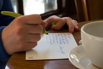 Postkartenschreiben im Café. Symbolbild für Text-Workshops von Laelia Kaderas.