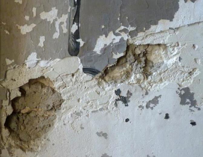 Détail de la partie inférieure d'un mur, chute de matière et Partie inférieure de « Moïse et le Buisson Ardent », fissure verticale dans le mur perte du décor