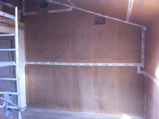 Pose du frein-vapeur, les lés sont jointés, dans les mêmes plans mais aussi murs et toit. Après la pose des liteaux, la ouate de cellulose pourra être insufflée
