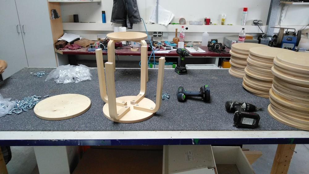 Zwei Hocker sind fertig. Rechts warten noch diverse Sitzfläche auf die Montage.