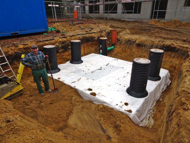 Wenn die Körbe eingepackt sind, wird das Loch zu geschüttet und das Regenwasser kann trotz versiegelter Fläche ins Grundwasser fließen.