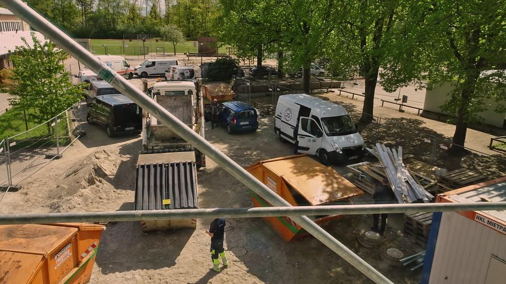 Hier sieht man, wie viele Leute auf der Baustellearbeiten. Haufenweise Autos auf der Baustelle. Auf der Straße und den Parkplätzen stehen auch noch welche.