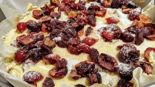 Impasto torta ricotta e ciliegie con spolverata di zucchero versato nella tortiera