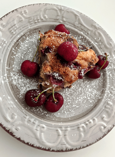 Torta ricotta e ciliegie servita sul piatto con zucchero a velo e ciliegie