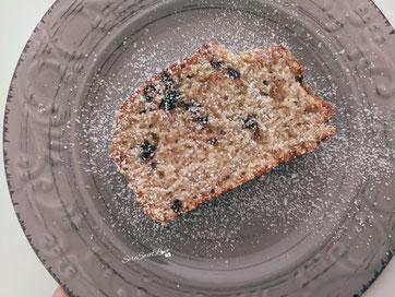 Banana Bread  con gocce di cioccolato fondente e spolverata di zucchero a velo servito sul piatto da dessert