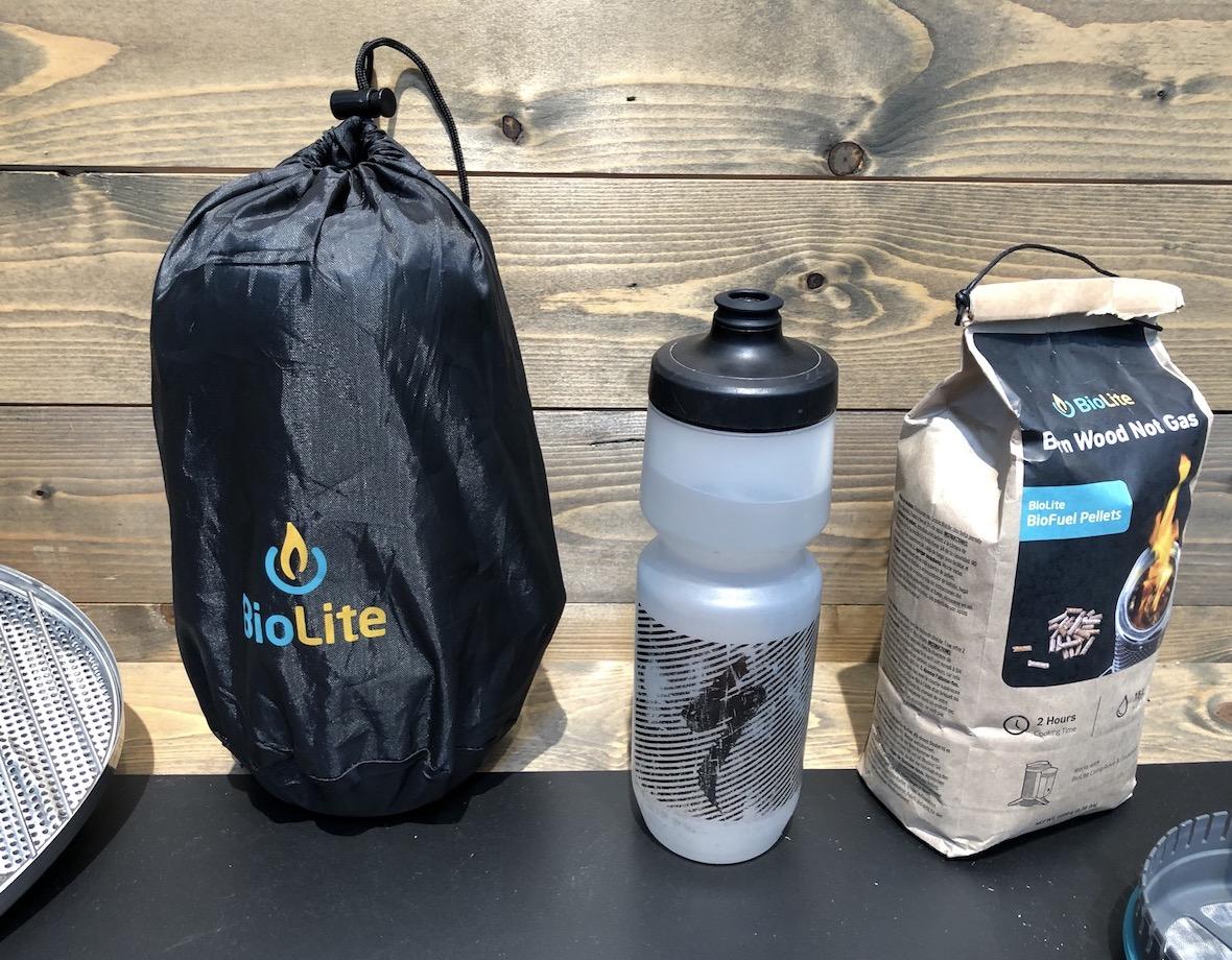 BioLite - Kocher zerlegt und im Topf verpackt. Die Trinkflasche zeigt den Größenvergleich