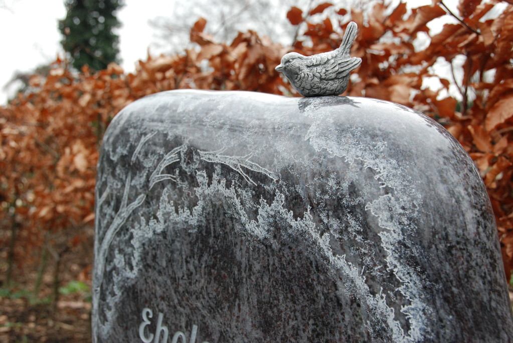 Grabstein aus Granit mit einem Vogel aus Aluminium