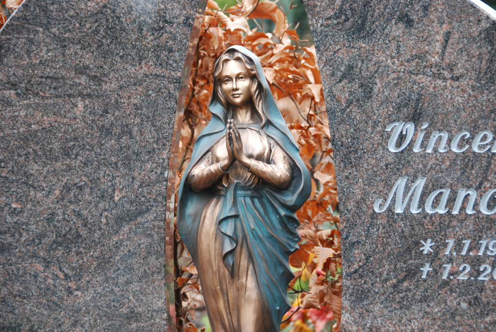 Grabstein aus Granit mit Bronze-Madonna im Detail
