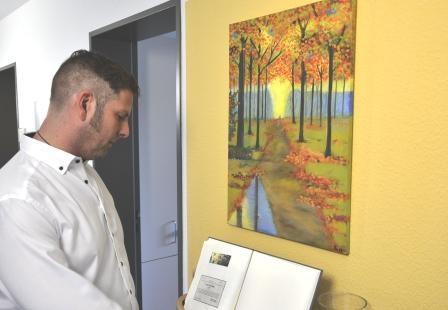 Pflegedienstleiter Simon Gerhard betrachtet das Gedenkbuch
