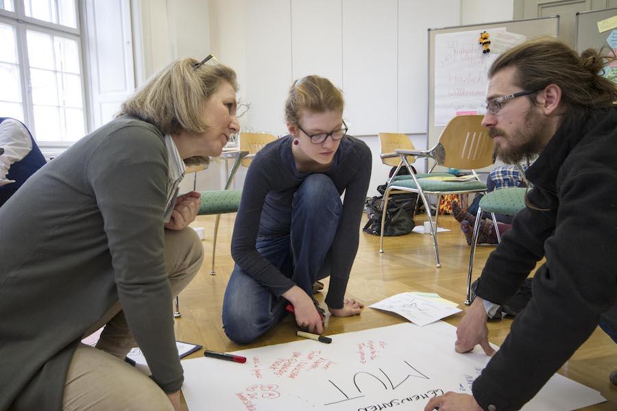 Teilnehmer der TZI Frühjahrswerkstatt erstellen ein Poster