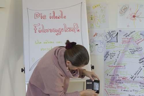 Teilnehmende fotografiert Plakate in einem TZI Kurs