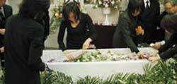 家族葬で柩のなかへお花を飾るご家族