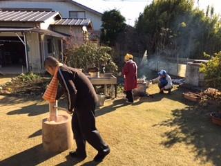 杵とうすでお餅つき 奥は薪で火を焚いています