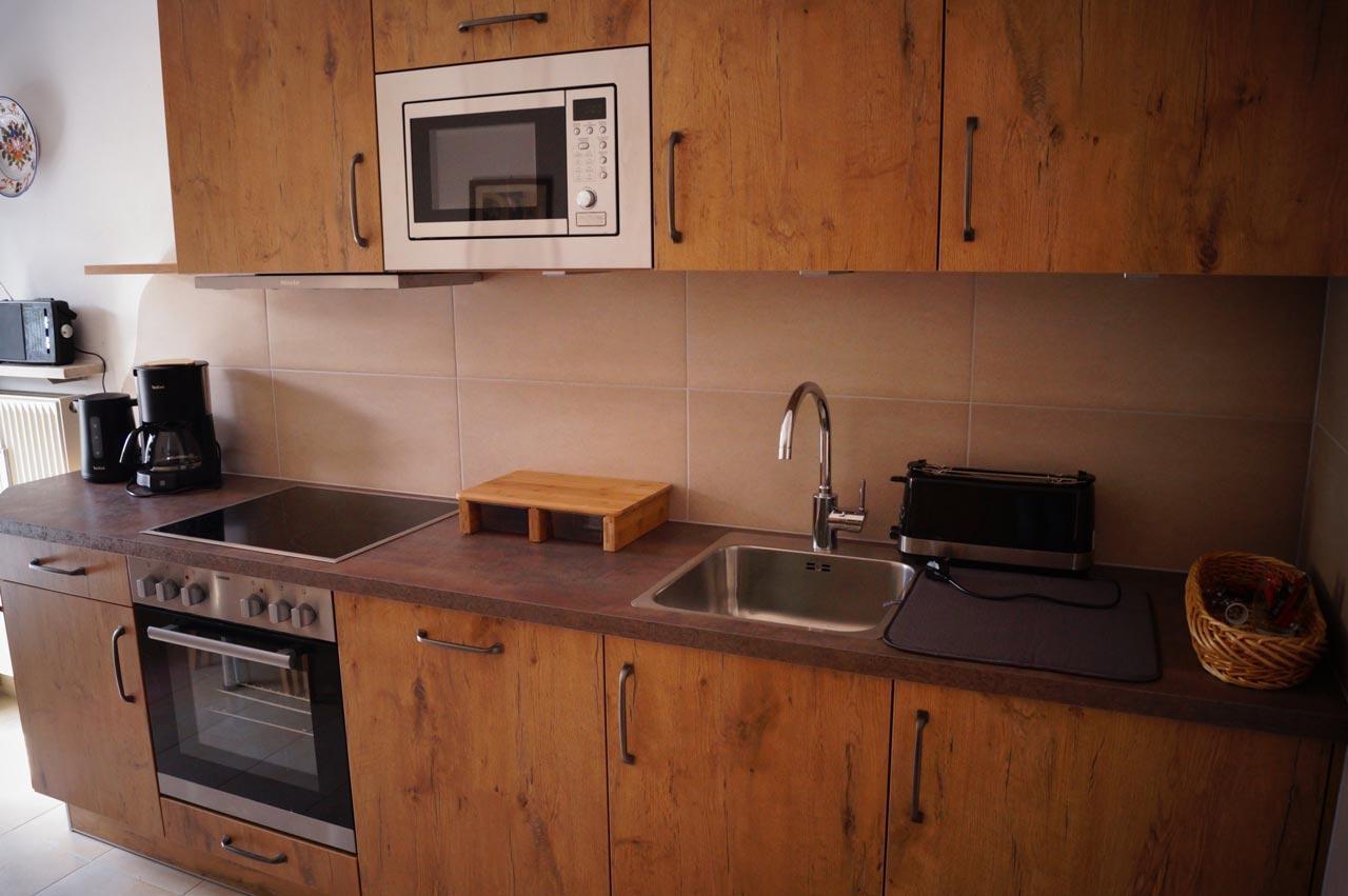 Neue Küchenzeile mit Mikrowelle, Backofen, Ceranfeld, Kühlschrank mit kleinem Gefrierfach, Toaster, Wasserkocher, Kaffeemaschine und Radio