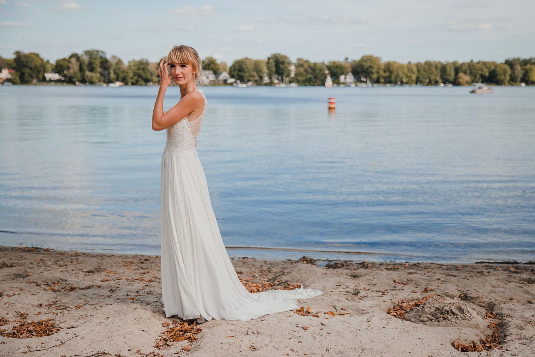 Braut in langem Brautkleid am See