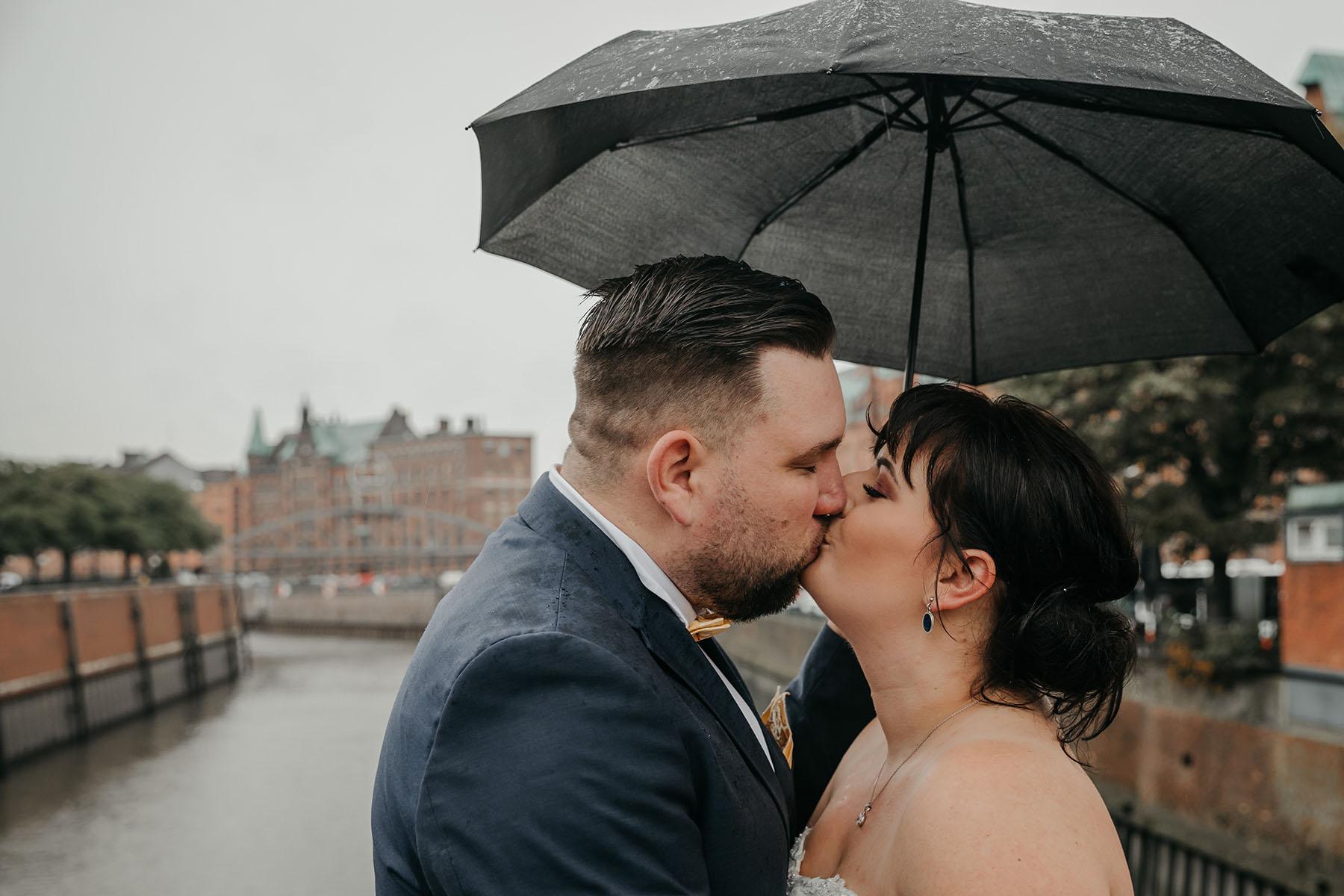 Hochzeit mit Regenschirm Brautpaarkuss in Hamburg