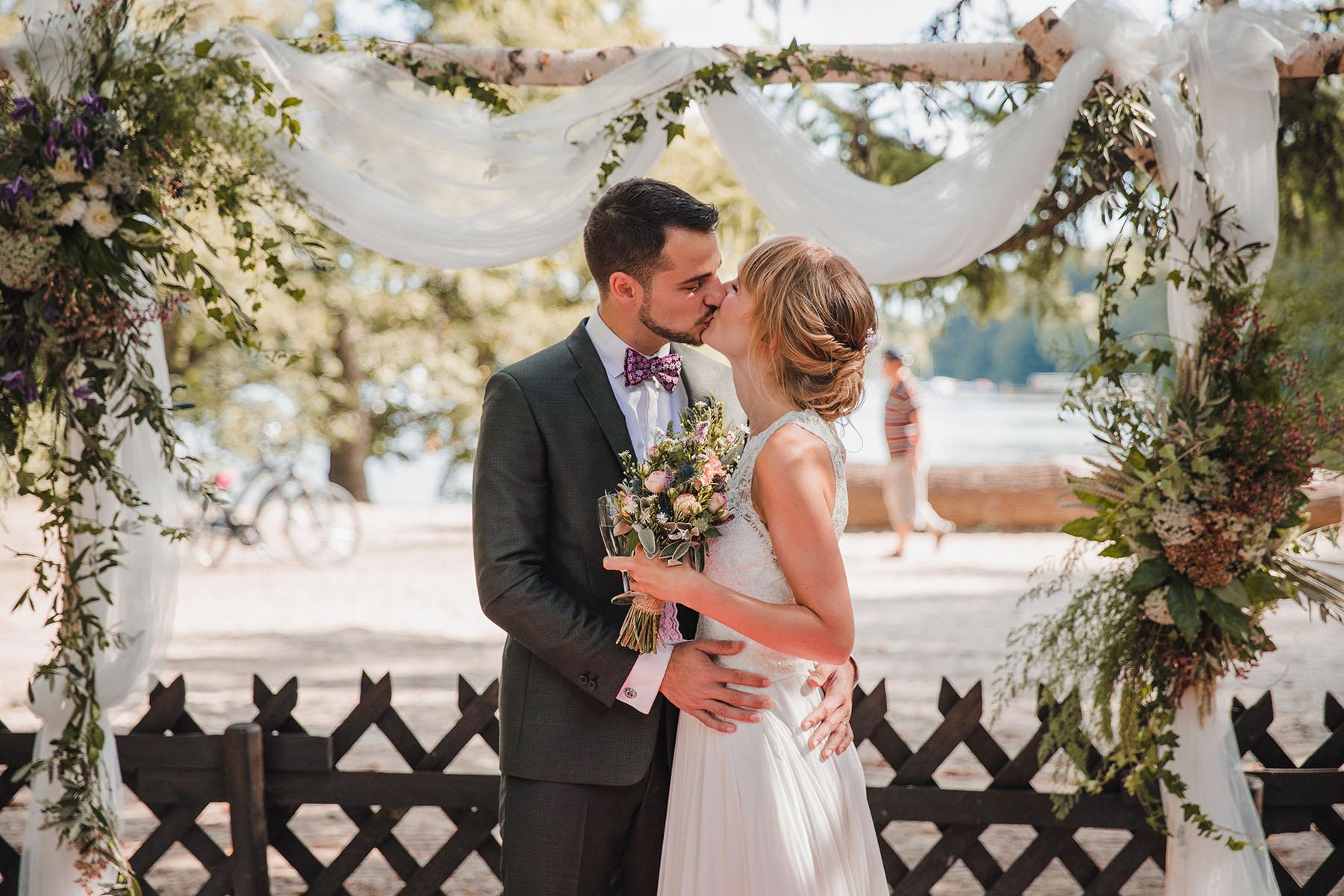 Brautpaar unterm Traubogen bei Freier Trauung