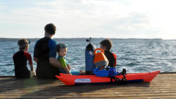 Family sitting at the edge of a dock with un-assembled STEPDive diving system