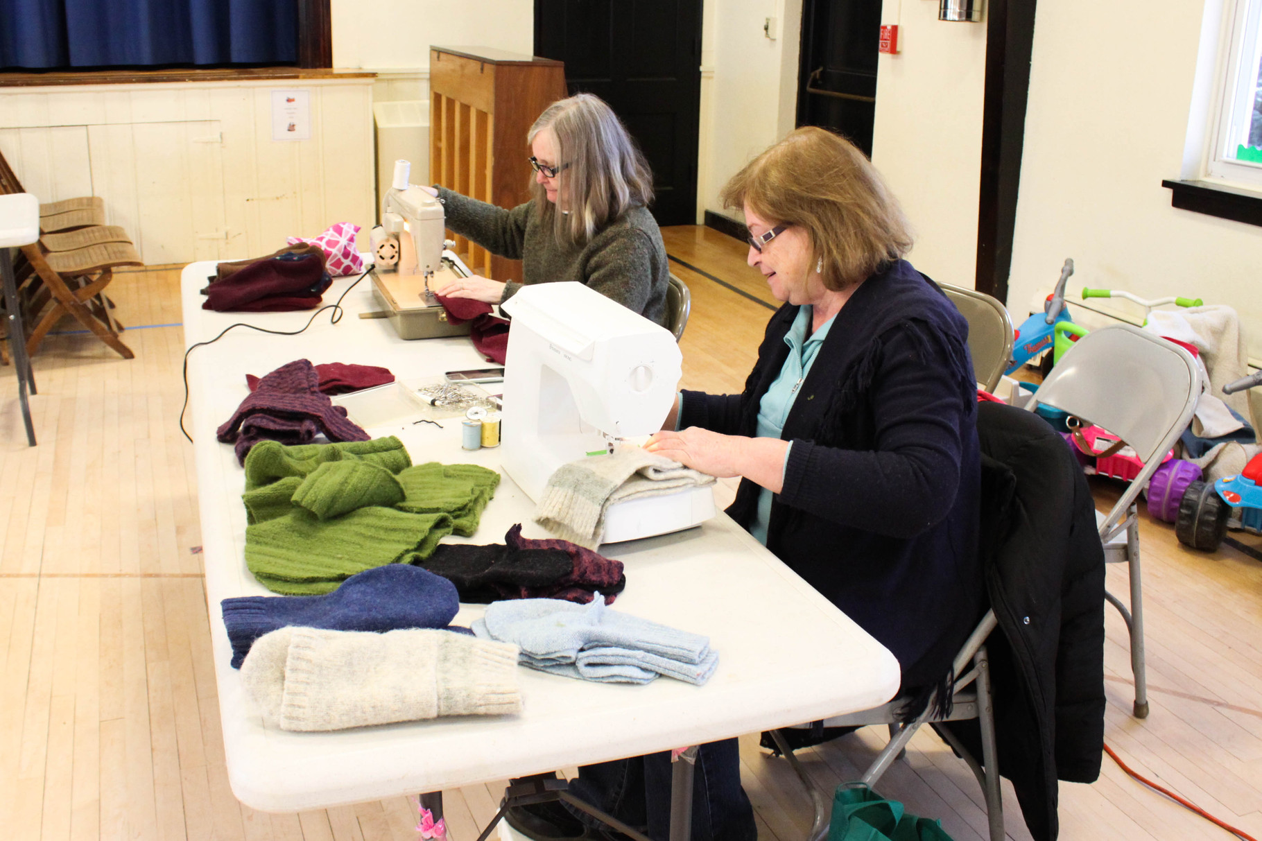 The sewing team makes the finishing touches to pairs of mittens