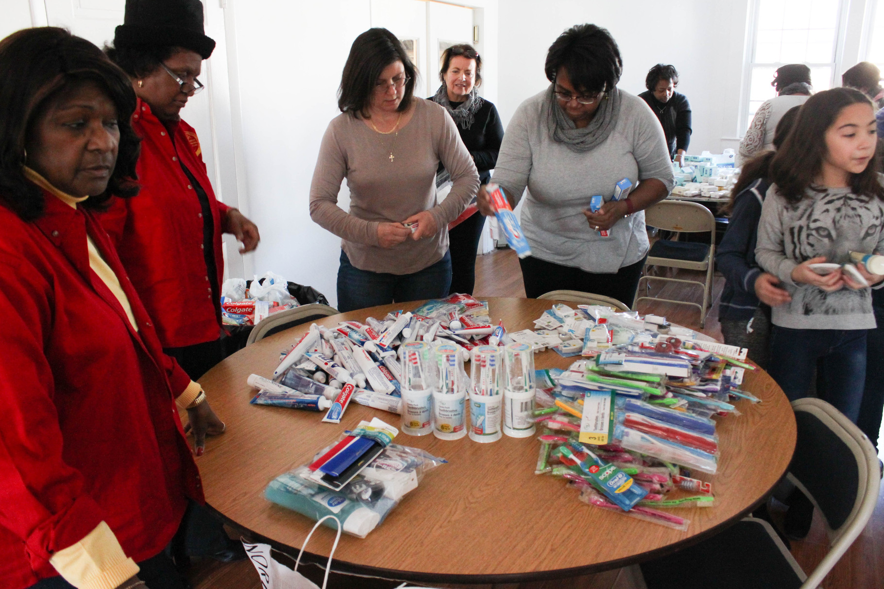 Volunteers sort toothpaste and toothbrushes